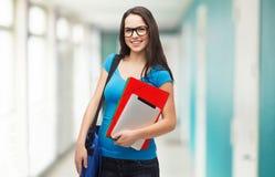 Estudiante sonriente con el bolso, las carpetas y PC de la tableta Foto de archivo