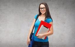 Estudiante sonriente con el bolso, las carpetas y PC de la tableta Imagen de archivo
