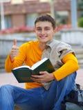 Estudiante sonriente con el libro y el pulgar para arriba Fotografía de archivo
