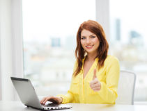 Estudiante sonriente con el ordenador portátil en la escuela Imagen de archivo libre de regalías