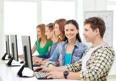 Estudiante sonriente con el ordenador que estudia en la escuela Imagen de archivo libre de regalías