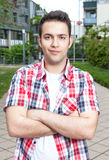 Estudiante sonriente con la camisa comprobada y los brazos cruzados Foto de archivo