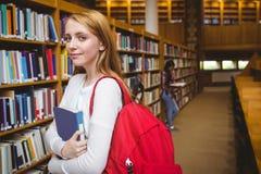 Estudiante sonriente con la mochila que sostiene un libro en biblioteca Foto de archivo