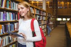 Estudiante sonriente con la mochila usando la tableta en biblioteca Imagen de archivo libre de regalías