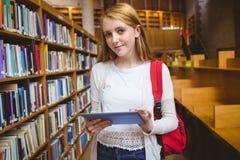 Estudiante sonriente con la mochila usando la tableta en biblioteca Imagen de archivo