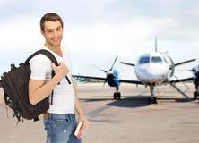 Estudiante sonriente con la mochila y el libro en el aeropuerto Imágenes de archivo libres de regalías