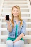Estudiante sonriente con la pantalla en blanco del smartphone Foto de archivo libre de regalías