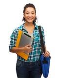 Estudiante sonriente con las carpetas, PC de la tableta y el bolso Imágenes de archivo libres de regalías