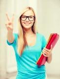 Estudiante sonriente con las carpetas que muestran la muestra de la victoria Imagen de archivo