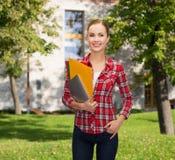 Estudiante sonriente con las carpetas y PC de la tableta Imagen de archivo