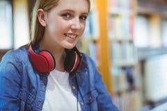 Estudiante sonriente con los auriculares que miran la cámara Fotos de archivo