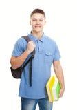 Estudiante sonriente con los libros y la mochila aislados en blanco Foto de archivo libre de regalías