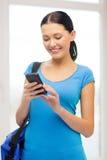 Estudiante sonriente con smartphone y el bolso Fotografía de archivo