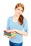 Estudiante sonriente con una pila de libros Imagen de archivo libre de regalías