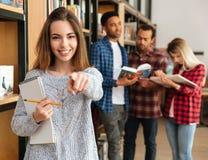 Estudiante sonriente de la chica joven que sostiene el libro de texto Foto de archivo libre de regalías