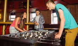 Estudiante sonriente de los amigos que juega a fútbol de la tabla en la competencia Foto de archivo libre de regalías