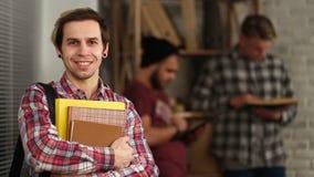 Estudiante sonriente del inconformista que celebra los libros en la biblioteca metrajes
