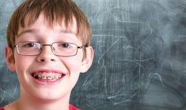 Estudiante sonriente delante de la pizarra Imagen de archivo libre de regalías