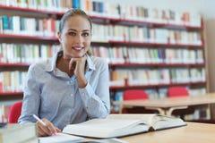 Estudiante sonriente en la biblioteca Foto de archivo
