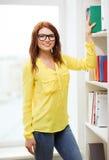 Estudiante sonriente en las lentes que eligen el libro Imagen de archivo libre de regalías