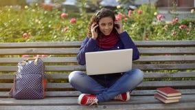 Estudiante sonriente en los auriculares que se sientan en el banco, escuchando la lista de temas preferida Imagen de archivo