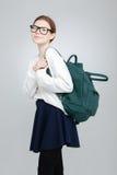 Estudiante sonriente en los vidrios que colocan y que sostienen la mochila verde Foto de archivo