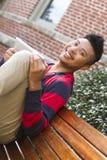 Estudiante sonriente en un banco Fotografía de archivo