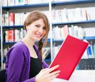 Estudiante sonriente en una biblioteca Fotos de archivo libres de regalías