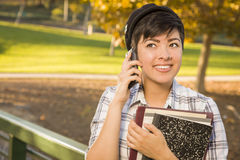 Estudiante sonriente Holding Books y el hablar de la raza mixta en el teléfono Fotos de archivo libres de regalías