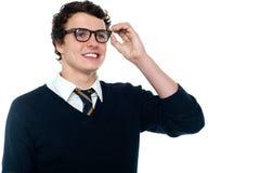 Estudiante sonriente que ajusta sus gafas Imagenes de archivo