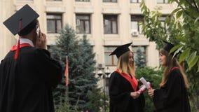 Estudiante sonriente que escucha los saludos sobre smartphone el día de graduación almacen de video