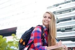 Estudiante sonriente que estudia afuera con la pluma y el libro Imágenes de archivo libres de regalías