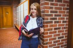Estudiante sonriente que estudia inclinarse contra la pared Fotografía de archivo