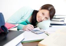 Estudiante sonriente que hace su preparación en un escritorio Fotografía de archivo libre de regalías