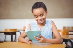 Estudiante sonriente que lee un libro Fotos de archivo