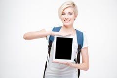 Estudiante sonriente que muestra la pantalla de tableta en blanco Imagen de archivo libre de regalías