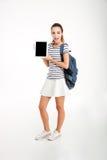 Estudiante sonriente que muestra la pantalla de tableta en blanco Imágenes de archivo libres de regalías