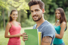 Estudiante sonriente que presenta en el parque Foto de archivo libre de regalías