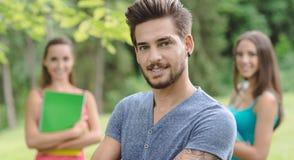 Estudiante sonriente que presenta en el parque Fotografía de archivo