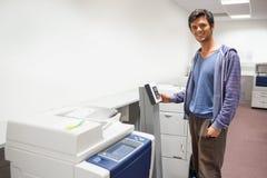 Estudiante sonriente que se coloca al lado de la fotocopiadora Fotos de archivo