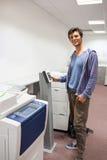 Estudiante sonriente que se coloca al lado de la fotocopiadora Foto de archivo libre de regalías