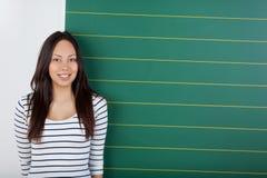 Estudiante sonriente que se coloca al lado de tablero Imágenes de archivo libres de regalías