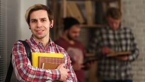 Estudiante sonriente que se coloca con el bolso y los cuadernos almacen de video