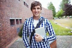 Estudiante sonriente que se coloca en campus con la tableta digital foto de archivo libre de regalías