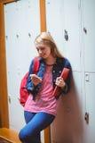 Estudiante sonriente que se inclina contra el armario usando smartphone Imagen de archivo