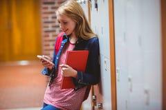 Estudiante sonriente que se inclina contra el armario usando smartphone Fotografía de archivo libre de regalías