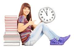 Estudiante sonriente que se inclina en una pila de libros y de señalar Foto de archivo libre de regalías