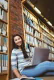 Estudiante sonriente que se sienta en el piso contra la pared en la biblioteca que estudia con el ordenador portátil y los libros Foto de archivo