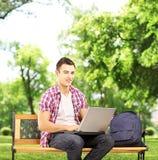 Estudiante sonriente que se sienta en un banco y que trabaja en un ordenador Imagenes de archivo