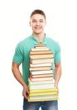 Estudiante sonriente que sostiene la pila grande de libros Foto de archivo libre de regalías